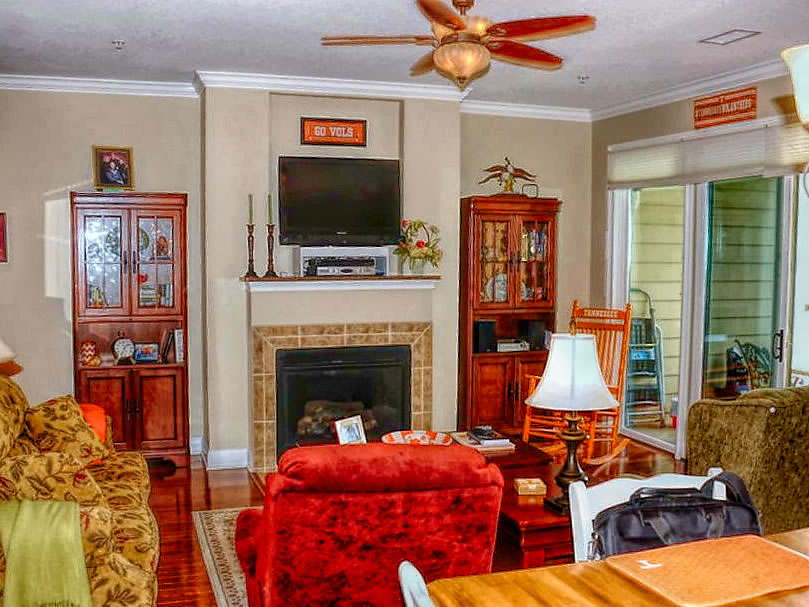 Living room with hardwood flooring, fireplace, ceiling fans, crown molding and more